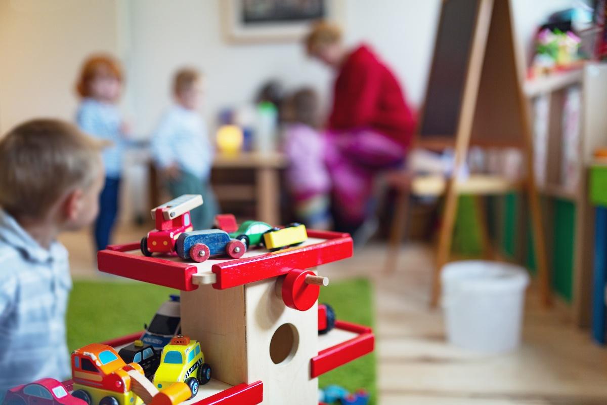 Kinderbetreung: Kind Spielt mit Holzautos